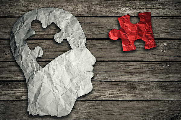 Puzzle head brain concept as a human face profile made from crumpled white paper with a jigsaw piece cut out on a rustic old wood background as a mental health symbol.
