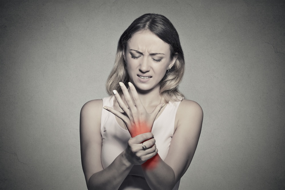 Young woman holding her painful wrist isolated on gray wall background. Sprain pain location indicated by red spot. Negative face expression