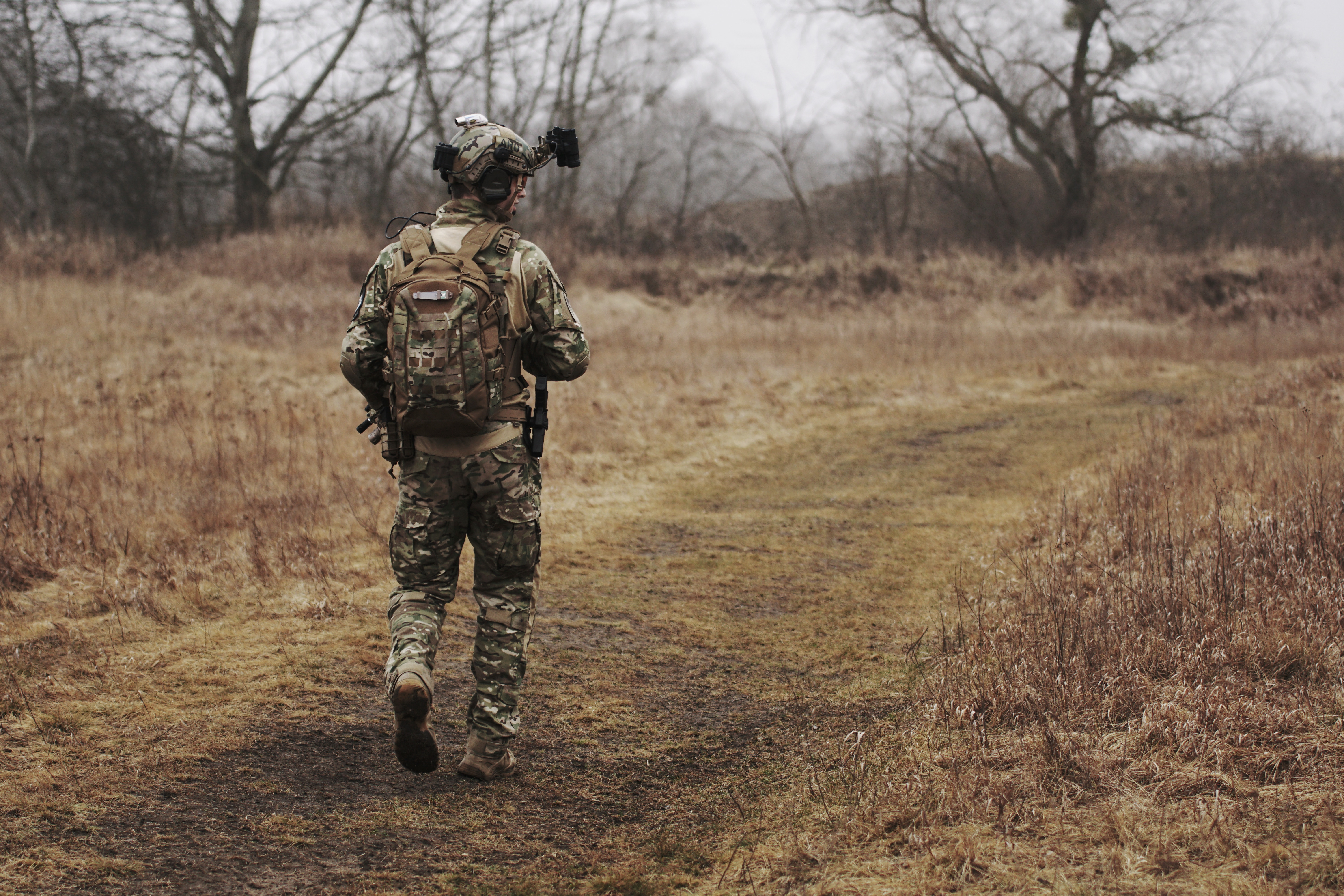military soldier walking alone through a field